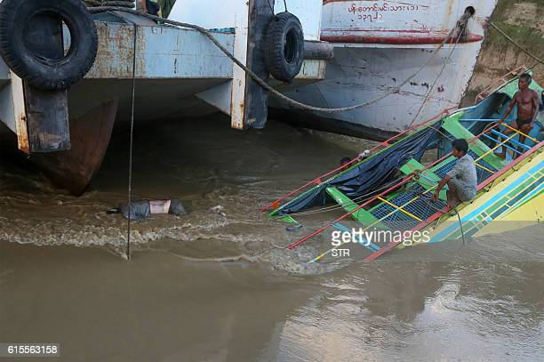 In this photograph taken on October 18 a body floats on the sunken ferry partially lifted from the water near the river's bank The death toll from a...