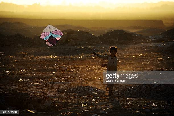 In this photograph taken on October 20 an Afghan child plays with a kite on the outskirts of Herat Afghanistan's economy has improved significantly...