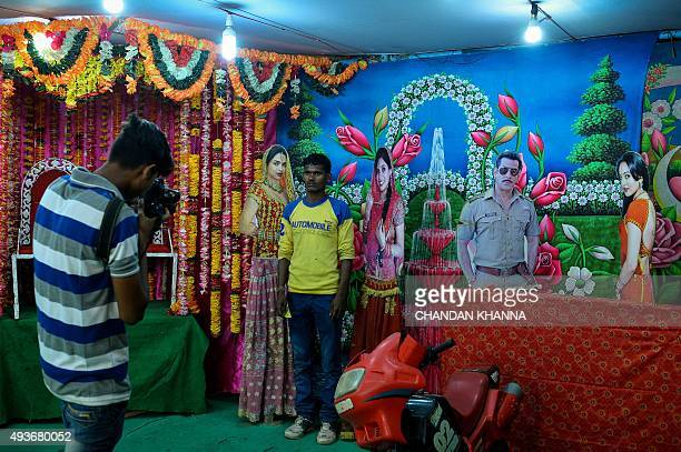 In this photograph taken on October 21 an Indian man poses for a picture inside a makeshift studio at a fair during celebrations of the Hindu...