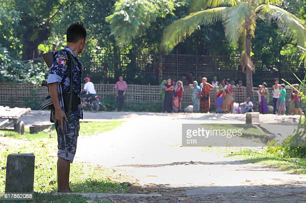 In this photograph taken on October 21 Muslim and Hindu residents wait for emergency vehicle to evacuate a pregnant woman in Ngakuya in Rakhine State...