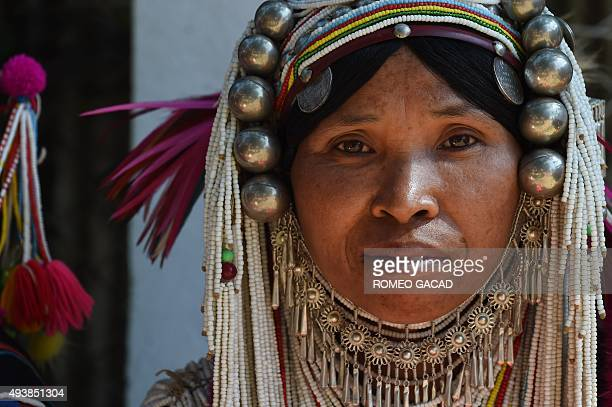 In this photograph taken on October 22 a Shan ethnic woman from the Akha hill tribe wearing traditional costumes and silver head cover ornaments...