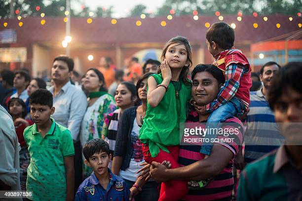 In this photograph taken on October 22 an Indian man holds his daughter and son so that they can get to see a stage at a fair during celebrations of...