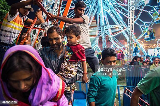 In this photograph taken on October 22 an Indian man holds his child as they exit a fair ride during celebrations of the Hindu 'Dussehra' festival in...