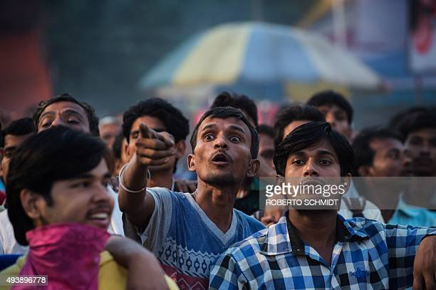 In this photograph taken on October 22 an Indian man points to a stage where actors portray a skit at a fair during celebrations of the Hindu...