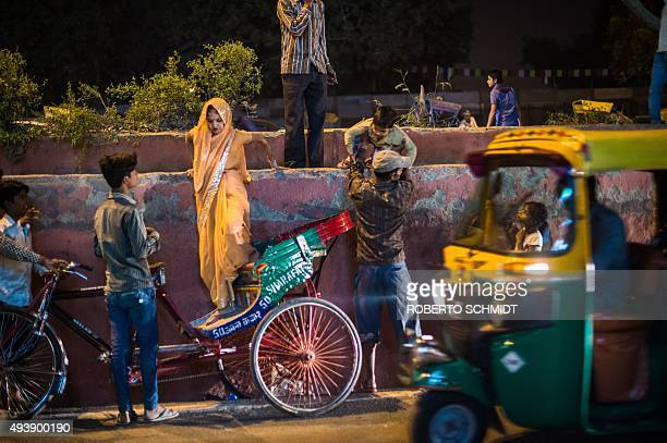 In this photograph taken on October 22 an Indian woman uses a cycle rickshaw parked on a side of a street to jump a median to reach the front gate of...