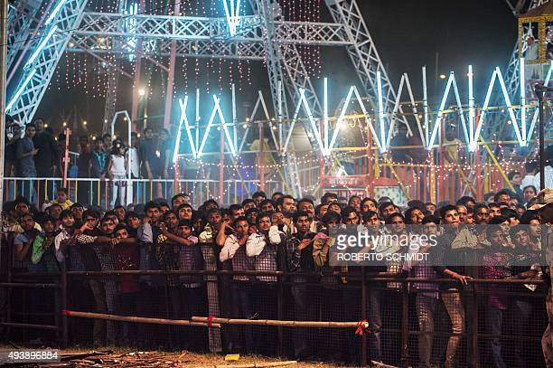 In this photograph taken on October 22 Indian men amass against a fence as they watch actors portray a skit at a fair during celebrations of the...