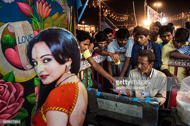 In this photograph taken on October 22 Indian men crowd to receive their photos at a portrait tent where participants can pose among other things...