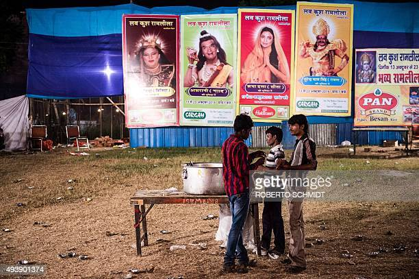 In this photograph taken on October 22 Indian men have a bite to eat near adverts showing actors posing as Hindu Gods at a fair during celebrations...
