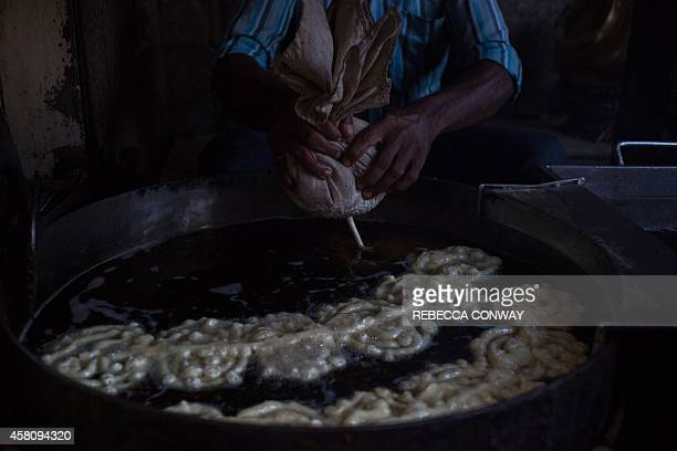 In this photograph taken on October 27 an Indian worker at Old Famous Jalebi Wala which sells jalebi sweets and samosas makes fresh jalebis fried...