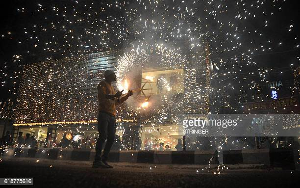 TOPSHOT In this photograph taken on October 27 an Indian worker bursts firecrackers during a fireworks display at a local marketplace on the eve of...