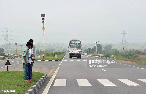 In this photograph taken on October 5 Indian Lambadi tribal students prepare to cross National Highway 44 to go to school in the village of...