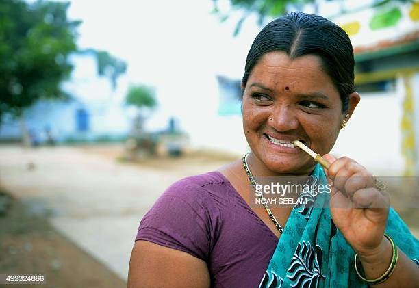In this photograph taken on October 5 Indian Lambadi tribal widow woman K Rukka who lost her husband in a road accident brushes her teeth with a neem...