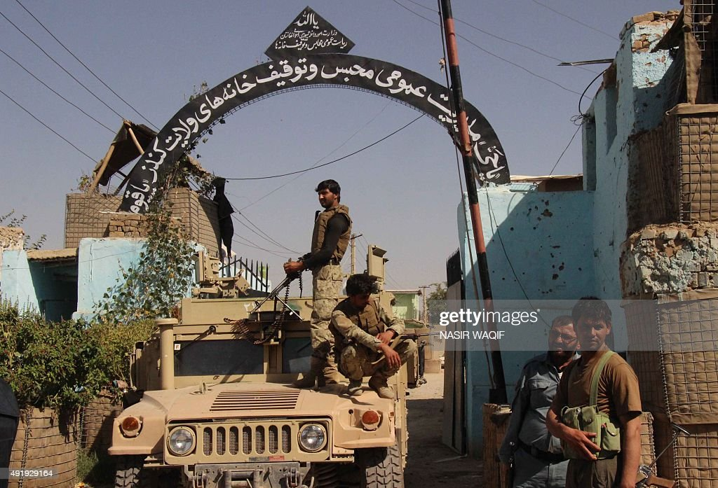 In this photograph taken on October 8 Afghan security forces stand guard at the main gate of the prison after retaking Kunduz from the Taliban in...