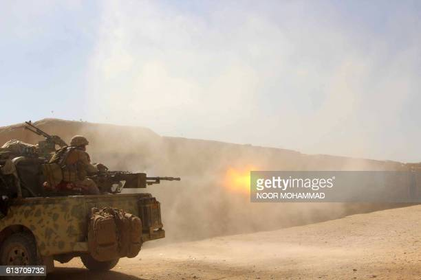 TOPSHOT In this photograph taken on October 9 Afghan National Army commandos open fire on a Taliban position during a military operation in Helmand...