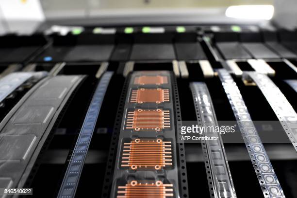 In this photograph taken on September 1 shows powering components in the process of Printed Circuit Board Assembly in a clean room of the Valeo...