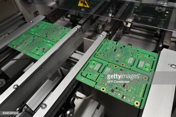 In this photograph taken on September 1 shows the process of Printed Circuit Board Assembly in a clean room of the Valeo factory in SableSurSarthe...