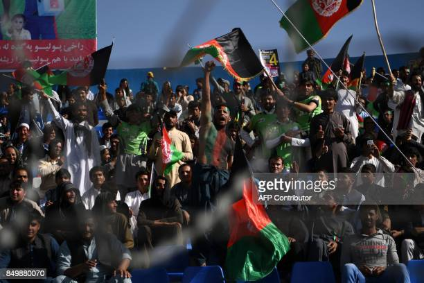 In this photograph taken on September 18 Afghan cricket fans cheer and wave the national flag during a match between Kabul Eagles and BandeAmir...
