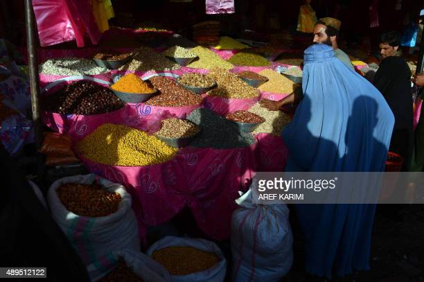 In this photograph taken on September 21 2015 an burqaclad Afghan woman buys dry fruits ahead of the sacrificial Eid alAdha festival in Herat...
