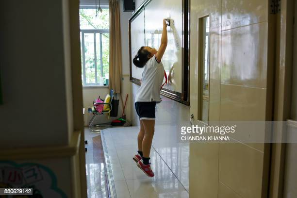 In this photograph taken on September 27 a student cleans the whiteboard inside her classroom at her school in Shanghai Western interest in China's...