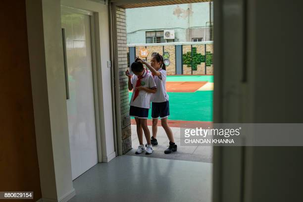 In this photograph taken on September 27 a student helps to adjust her friend's hair at their school in Shanghai Western interest in China's school...