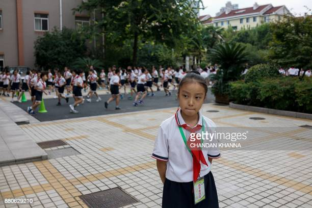 In this photograph taken on September 27 a student looks on as others take part in a physical training session at their school in Shanghai Western...