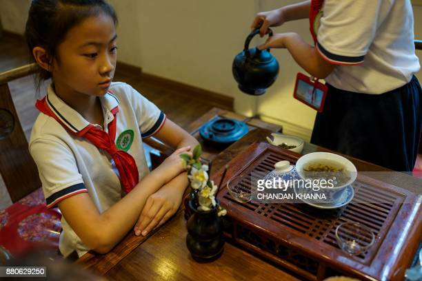 In this photograph taken on September 27 a student looks on as traditional Chinese tea is prepared during an activity session at her school in...