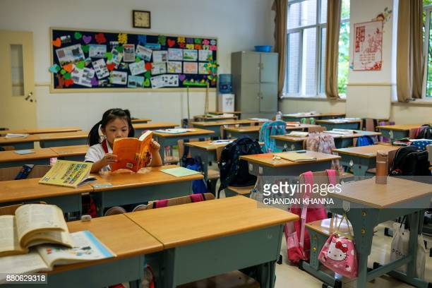 In this photograph taken on September 27 a student sits in her classroom as she reads at her school in Shanghai Western interest in China's school...