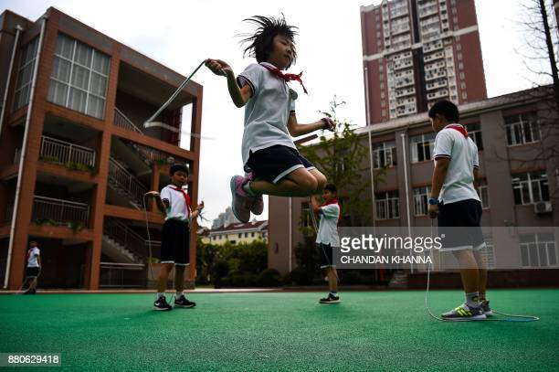 In this photograph taken on September 27 a student skips rope in the playground during a physical training session at her school in Shanghai Western...
