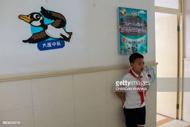 In this photograph taken on September 27 a student stands outside his classroom at his school in Shanghai Western interest in China's school system...
