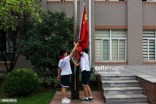 In this photograph taken on September 27 students adjust the national flag in the playground during a flaghoisting ceremony at their school in...