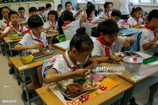 In this photograph taken on September 27 students eat their lunch during the lunch break at their school in Shanghai Western interest in China's...