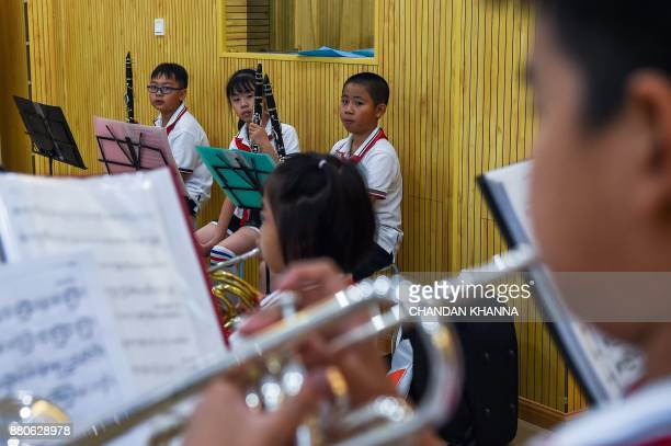 In this photograph taken on September 27 students look on as they play Western musical instruments during a Western music session at their school in...