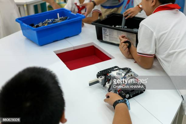 In this photograph taken on September 27 students make toy robots during an activity session at their school in Shanghai Western interest in China's...