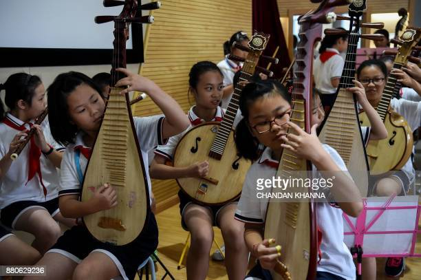 In this photograph taken on September 27 students play Chinese musical instruments during a Chinese music session at their school in Shanghai Western...