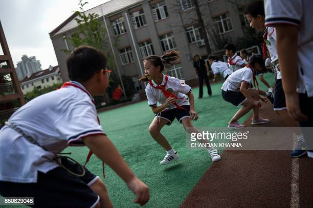 In this photograph taken on September 27 students run in the playground during a physical training session at their school in Shanghai Western...
