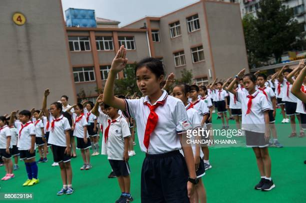 In this photograph taken on September 27 students sing the national anthem in the playground during the flaghoisting ceremony at their school in...
