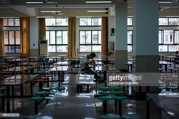 In this photograph taken on September 28 a student eats his lunch in his school in Shanghai Western interest in China's school system and Shanghai in...