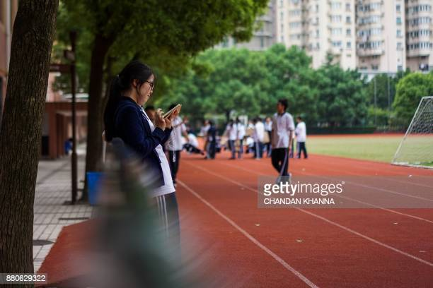 In this photograph taken on September 28 a student looks at her phone while others play during their physical training session in their school in...