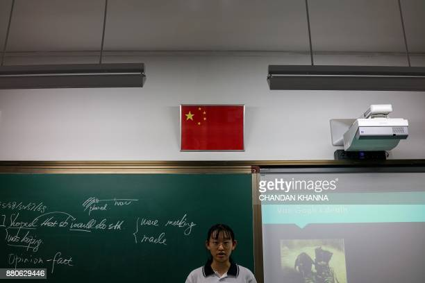 In this photograph taken on September 28 a student stands below the Chinese flag in a classroom in her school in Shanghai Western interest in China's...