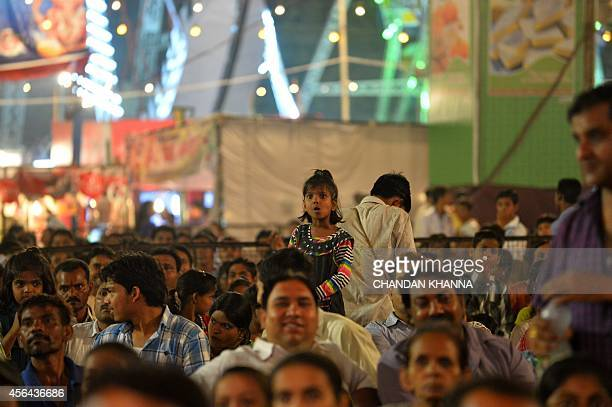 In this photograph taken on September 30 an Indian child watches a 'Ramleela' play at a fair to celebrate the Dusshera festival in New Delhi With...