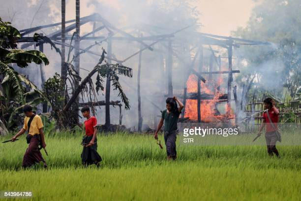 TOPSHOT In this photograph taken on September 7 unidentified men carry knives and slingshots as they walk past a burning house in Gawdu Tharya...
