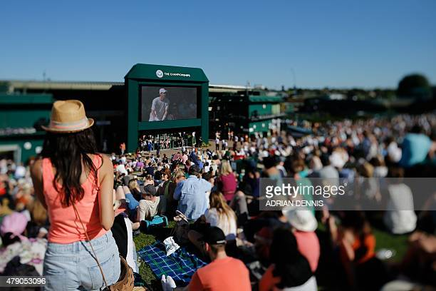 In this photograph taken with a tiltshift lens visitors are seen sitting on Murray Mound while watching a giant screen showing Britain's Andy Murray...