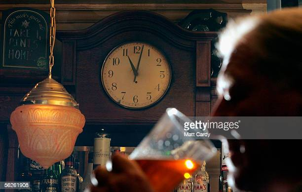 In this photoillustration A man drinks as the pub clock passes 11pm signalling 'time at the bar' in a traditional public house the Star Inn on...
