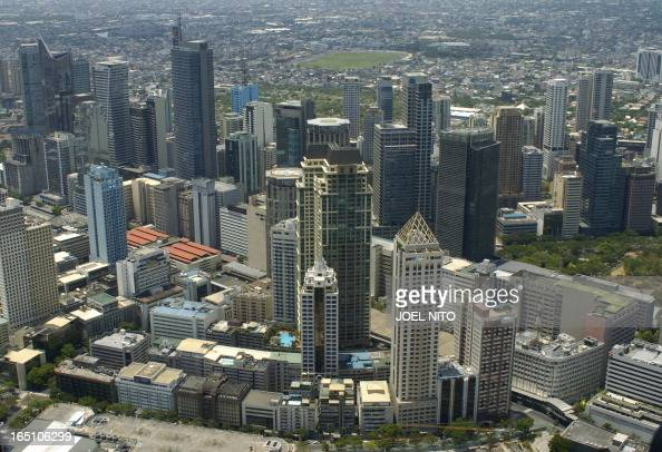 In this picture dated 01 May 2006 highrise buildings in the Philippine financial district of Manila loom over a landscape of smaller houses...