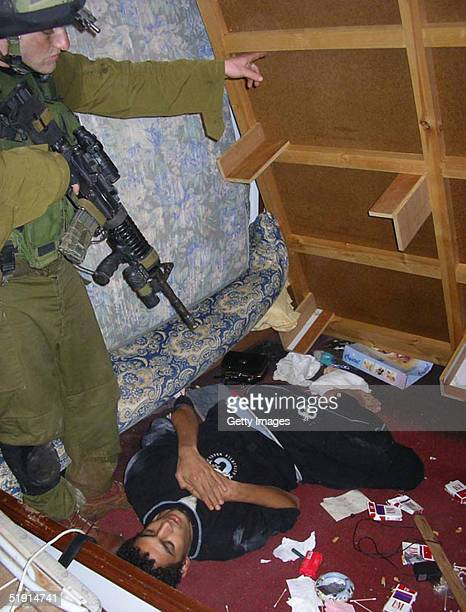 In this picture made available by the Israeli Defence Forces Israeli soldiers find wanted Islamic jihad militant Bilal Yassin hiding in a space under...