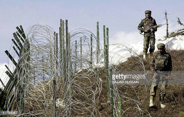 In this picture taken 04 December 2003 Indian soldiers patrol along a barbedwire fence near Baras Post on the Line of Control between Pakistan and...