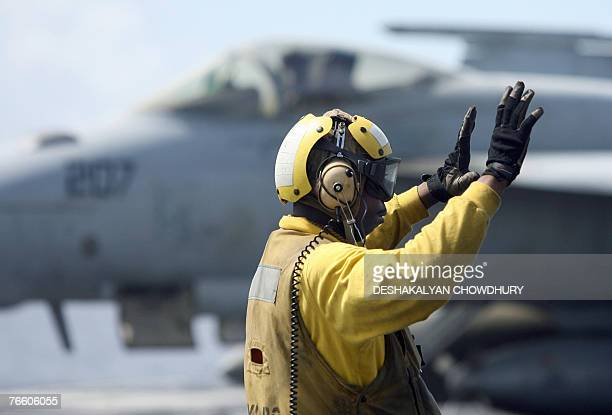 MILITARY In this picture taken 07 September 2007 a US Navy crewman gestures to a pilot on the deck of USS Kitty Hawk aircraft carrier in the Bay of...