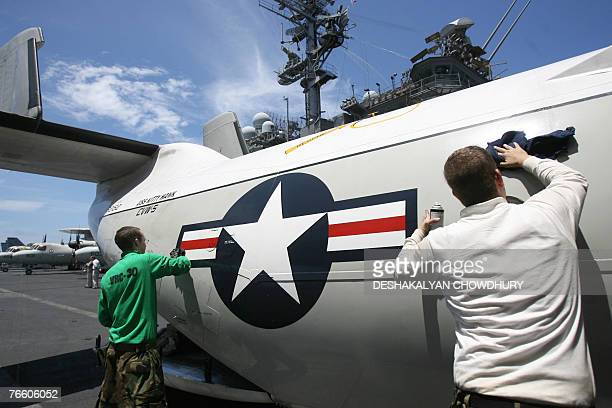 MILITARY In this picture taken 07 September 2007 US Navy crew clean the fuselage of a C2AGreyhound Carrier on Board aeroplane on the deck of USS...