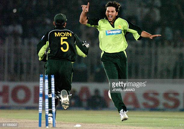 In this picture taken 16 March 2004 Pakistani cricketers Shahid Afridi and Moin Khan celebrate the dismissal of Indian captain Sourav Ganguly during...