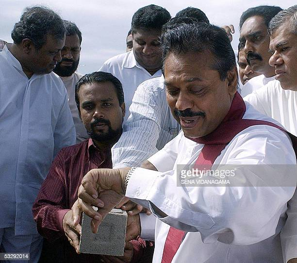 In this picture taken 19 January 2005 Sri Lankan Prime Minister Mahinda Rajapakse checks his watch as he prepares to lay the foundation stone for a...